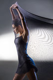 Graceful brunette stretches stretch mesh fabric over itself agai Stock Photography