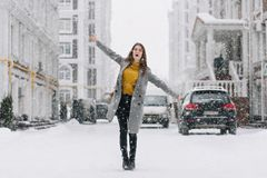 Graceful caucasian female model in long coat dancing on the street in winter morning. Outdoor photo of charming lady in. Yellow sweater waving hands during royalty free stock photos