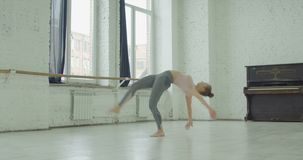 Elegant sporty woman doing cartwheel exercise. Graceful charming woman in sportswear working out, doing cartweel and split exercise while warming up in dance stock footage