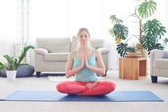 Graceful chestnut meditating while sitting on yoga mat Royalty Free Stock Photo