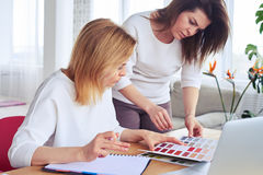Graceful concentrated females looking through catalog of color p Stock Images