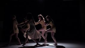 Graceful contemporary dance of five dancers in white clothes on black, shadow, slow motion