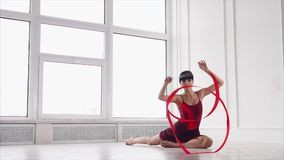 Graceful dance with ribbon. Slow motion shot of graceful woman dancing with ribbon in the studio. She doing elements sitting on the floor stock video footage