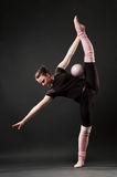 Graceful dancer with ball. Against dark background Stock Image