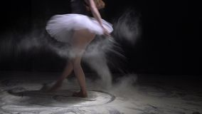 Graceful girl in tutu throwing dust in the dark. Graceful dancer in ballet tutu throwing white dust and jumping in the dark room stock video
