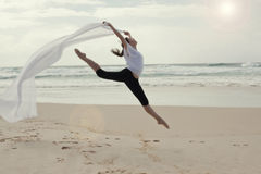 Graceful dancer on beach. Side view of graceful teenage dancer leaping midair on beach trailing white material, sea in background Stock Photos