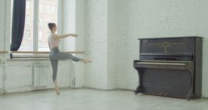 Ballerina performing battement fondu exercise. Graceful elegant ballerina performing battement fondu exercise during rehearsal in ballet studio. Charming classic stock footage