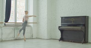 Ballerina performing battement frapper exercise. Graceful elegant ballerina performing battement frapper exercise during rehearsal in ballet studio. Charming stock footage
