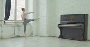 Ballerina performing dedans exercise at barre. Graceful elegant ballerina performing dedans exercise during rehearsal in ballet studio. Charming classic ballet stock footage