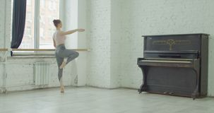 Ballerina performing dehors exercise at barre. Graceful elegant ballerina performing dehors exercise during rehearsal in ballet studio. Charming classic ballet stock video