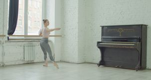 Ballerina performing demi rond exercise at barre. Graceful elegant ballerina performing demi rond exercise during rehearsal in ballet studio. Charming classic stock video