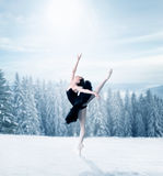 Graceful female ballet dancer stretching. Winter snowy forest on background Stock Images