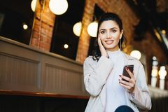 Graceful female with dark hair and eyes sitting in cafe using fr royalty free stock image