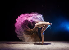 Graceful female gymnast in cloud of color dust Royalty Free Stock Photos