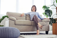 Graceful female having rest on sofa in bright living room Stock Photos