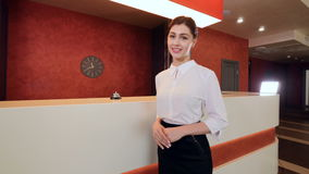 Graceful female receptionist is standing in hotel lobby and smiling.