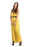 Graceful feminine fashion model in yellow dress posing at camera Stock Photos