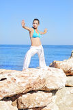 Graceful girl ashore epidemic deathes concerns with yoga Stock Images