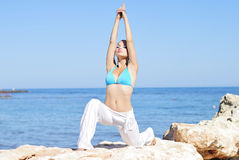 Graceful girl ashore epidemic deathes concerns with yoga Stock Photography