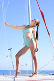 Graceful girl in blue swimsuit on sailboat Stock Images
