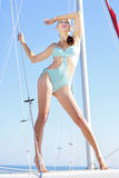Graceful girl in blue swimsuit on sailboat Royalty Free Stock Photography