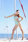 Graceful girl in blue swimsuit on sailboat Stock Photo