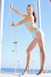 Graceful girl in blue swimsuit on sailboat Royalty Free Stock Photos