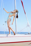 Graceful girl in blue swimsuit on sailboat Stock Photos