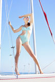 Graceful girl in blue swimsuit on sailboat Royalty Free Stock Photo