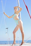 Graceful girl in blue swimsuit on sailboat Royalty Free Stock Image