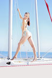 Graceful girl in blue swimsuit on sailboat Stock Image