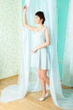 Graceful girl and curtain Stock Images