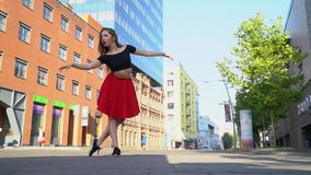 Graceful girl dances in a red skirt and black topic in the middle of the square in the summer day, slow motion stock video