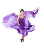 Graceful girl in flying purple silk dress Royalty Free Stock Image