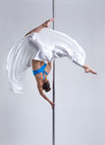 Graceful girl hanging upside down on pylon. Studio shot Stock Photo