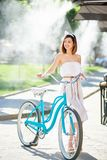 Graceful girl holds blue vintage bicycle in the summer. A graceful girl in a light dress holds a blue vintage bicycle and looks to the side in the background of Royalty Free Stock Photo