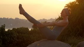 Girl in tracksuit does boat yoga pose on rock slow motion. Graceful girl in tracksuit does boat yoga pose on huge grey rock against pictorial sunrise and green stock video