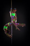 Graceful go-go dancers posing on pole in studio Royalty Free Stock Image