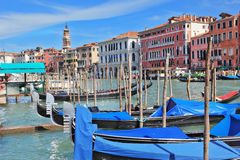 Graceful gondolas wait for passengers on the mooring Royalty Free Stock Images