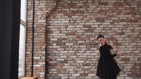 Graceful and graceful lady engaged in contemporary dance in the studio. Young woman in black dress is engaged in dancing on a brick wall background, lady stock video footage