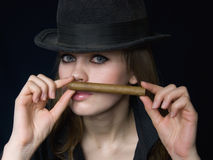 Graceful lady in black and a cigar. Graceful lady in a hat and a cigarette in a hand Stock Photos