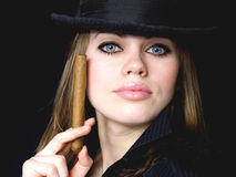 Graceful lady in black and a cigarette. Graceful lady in a hat and a cigarette in a hand Royalty Free Stock Photo