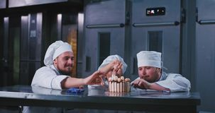 A graceful lady and two baker men wearing chefs attire , are excited when they start picking at this ravishing birthday. Cake. 4k stock video footage