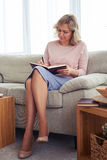 Graceful madam of age 30-40 writing letter while sitting on sof Stock Photo