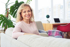Graceful madam smiling having rest while sitting on sofa Stock Photos