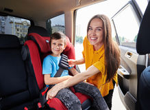 Graceful mom checking son sitting in baby seat Stock Images