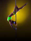 Graceful pole dancer posing under UV light Royalty Free Stock Photography