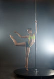 Graceful pole dancer in rays of spotlights Stock Image