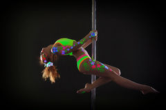 Graceful red-haired young woman dancing on pole Royalty Free Stock Photography
