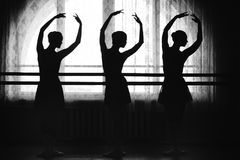 Graceful silhouettes of ballerinas on a window background. Graceful silhouettes of ballerinas in the background of a window in ballet class Royalty Free Stock Photography